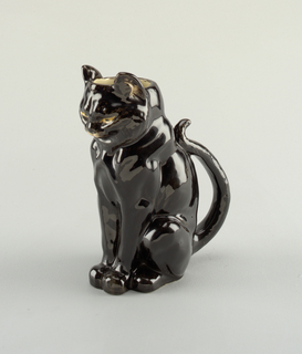 Figure of seated cat, upturned tail forming handle; top of head open; exterior body glazed black, eyes yellow, muzzle white. Interior clear-glazed over light cream body.