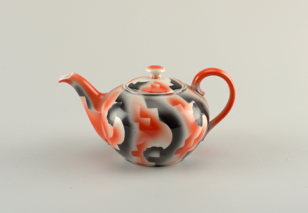 Teapot with atomized red and black glaze in amorphous design on a white ground.