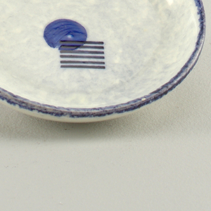 Dish in speckled beige and blue ground with blue rim containing blue circles with overlapping column of black stripes.