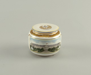 Cylindrical, rounded at base and top, disk-shaped lid; painted in polychrome enamel, ribbon border around top of body, emblem on lid. The front depicts a white building [Smolney?] of two storeys with fountains on the left and right; the back is the Pushkin Theatre, formerly Alexandrine Theatre or Alexandrinsky, flanked by trees.
