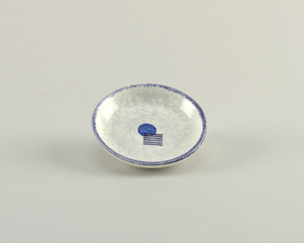 Round dish with a blue rim and decorated with a solid blue circle in the center with 6 short black stripes overlapping it.