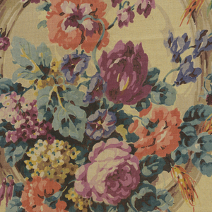 Polychrome block print on yellow linen. Rows of brown oval frames containing purple flowers, orange flowers, and clusters of purple and yellow flowers with blue-gren leaves. An alternate row of frames with similar flowers complete the repeat.