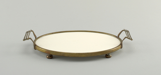 Round flat tray, undecorated white surface. Simple metal rim on bun feet, and handles.