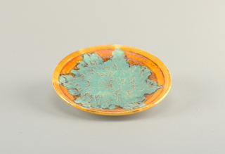 Round plate with flat orange rim. At center, amorphous green glaze with orange details resembling cracks.