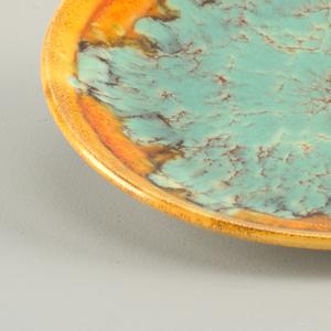 Round plate with flat orange rim. At center, amorphous green glaze with orange details resembling cracks.