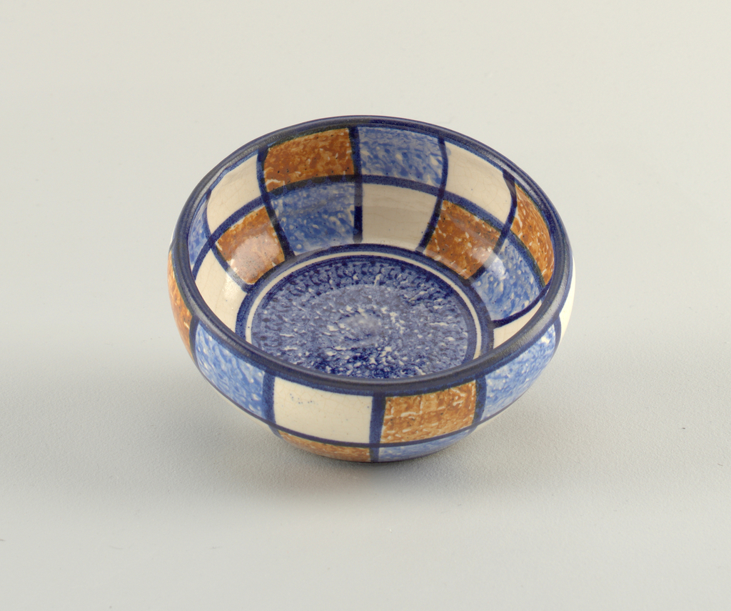 Circular bowl curving inwards at top edge.  Lines of blue at top and bottom edges.  Blue lines also divide the interior and exterior surfaces into a grid of white, blue, and brown patches.  Bottom of the interior is decorated with a darker blue circle surrounded by thin lines of white and blue.