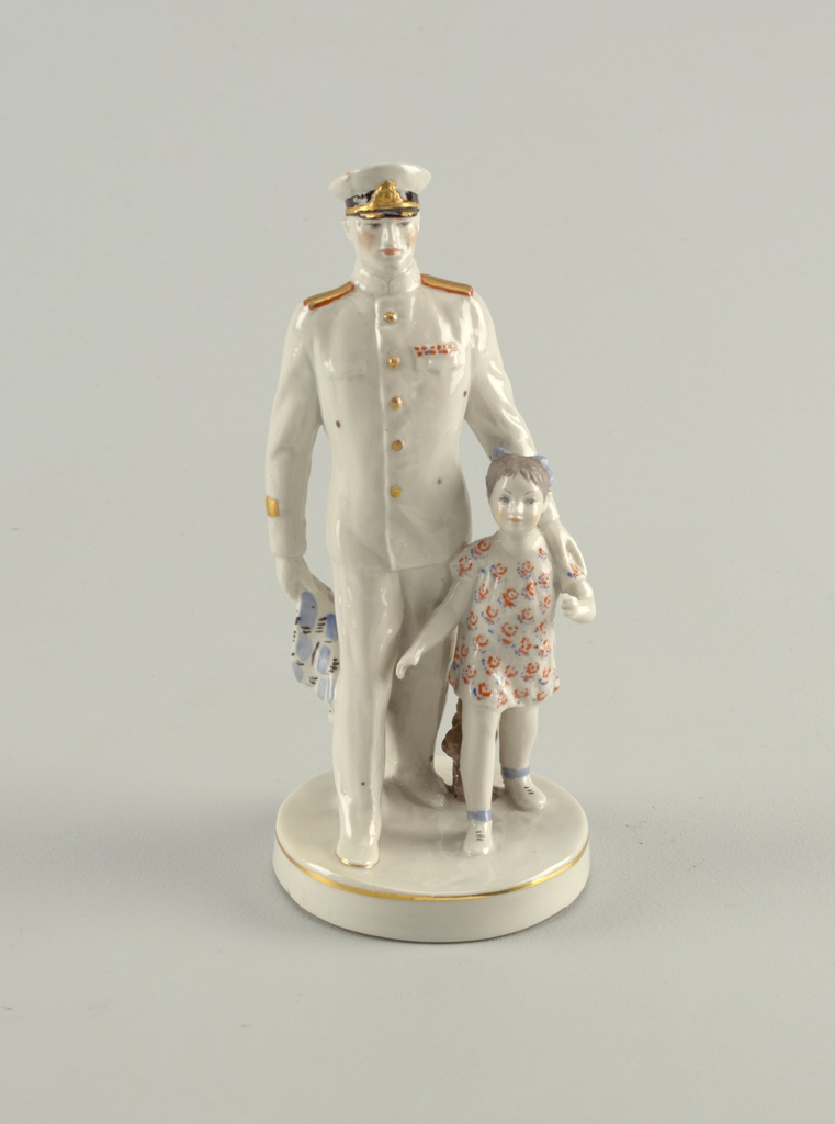 Man in white military uniform strides forward with right foot and with left arm holds on to small girl in flowered dress; circular base with gilt rim.