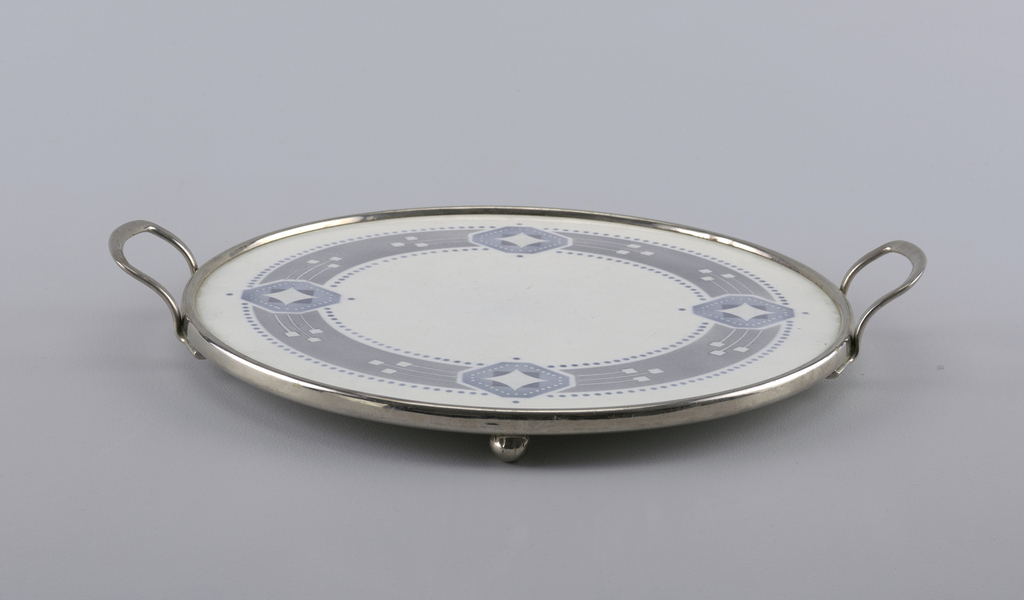 Flat round tray with blue diamond pattern. Smooth metal rim with handles and ball feet.