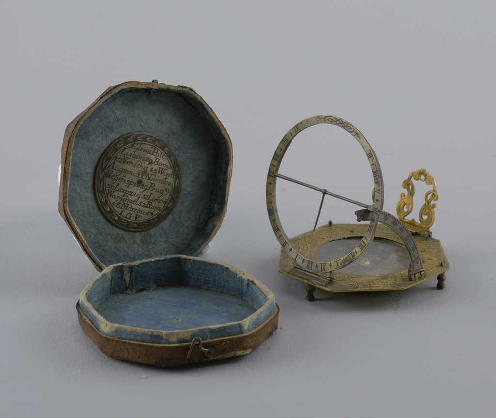Octagonal engraved brass disc on three feet; in center, sunk compass. On one side hinged, scrolled frame for missing pendulums. On other side, a hinged graded circle segment for setting latitudes. On third side, hinged ring with hours, and cross bar with needle. B) Octagonal case covered with brown leather and lined with blue silk. Disc with engraved named and latitudes of important cities inside cover.