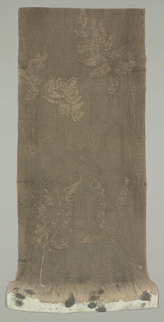 Kimono fragment of ribbed silk patterned using natural dyes of brown and black. Pattern made by pressing silk against wild grass and wood grain.