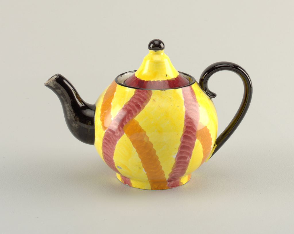 Circular body with c-shaped handle and curving s-shaped spout.  Handle, spout, and upper edge all painted black.  Yellow background with connecting, irregular stripes of orange and burgundy.  Conical lid surmounted by a black round finial.  Lid is also yellow, with a line of black on the edge with a bordering line of burgundy.