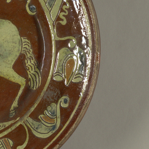 Deep circular dish. Incised slip decoration showing a horse and rider with sword charging to left. Symmetrical border. Pale green, sienna and blue on reddish-brown ground under a clear glaze.