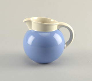 Bulbous, fishbowl-shaped body colored sky blue.  C-shaped white handle attached to body at bottom and top coming off the white vertical circular top.  Top is slightly slanted down from spout to handle at other end.
