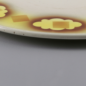 Flat circular plate with atomized and hard lined glaze decoration showing cloud forms and squares.