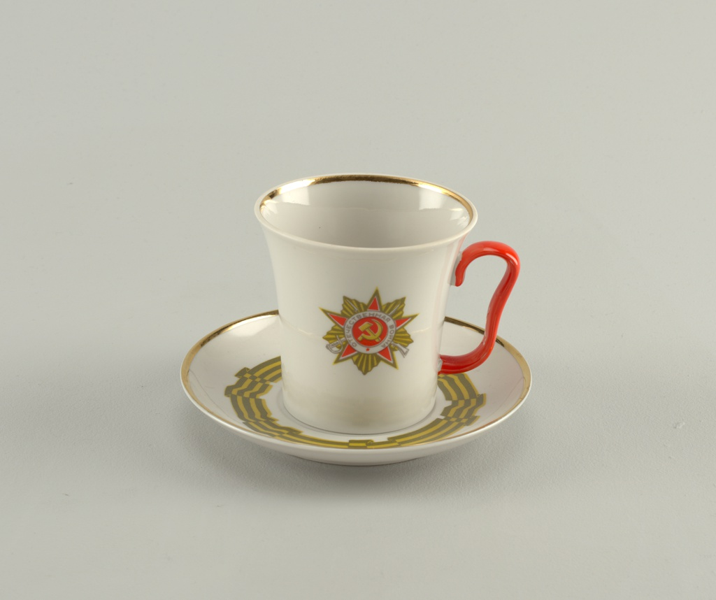 "Cup (a) cylindrical, flaring towards top, red loop handle; insignia painted on one side inscribed (in Russian) ""The Patriotic War."" The saucer (b) painted with folded striped ribbon circling border."