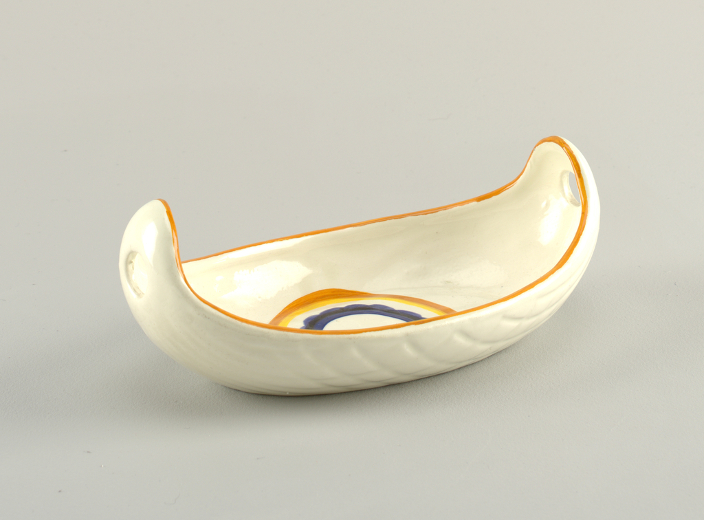 Boat-shaped dish.  Oval form with raised curving ends, each with a circular hole.  Exterior molded pattern on both sides of lines radiating from the ends and a central basket weave pattern.  Cream background with an orange top edge.  Central design in bottom of dish consists of concetric circles in orange, yellow, white, royal blue with a scalloped edge, dark blue, royal blue, and a solid cream center.