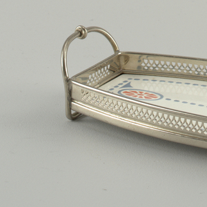 Rectangular plate swelling at center. Glazed in blue and red with dash motif. Pierced basket and rounded handles.