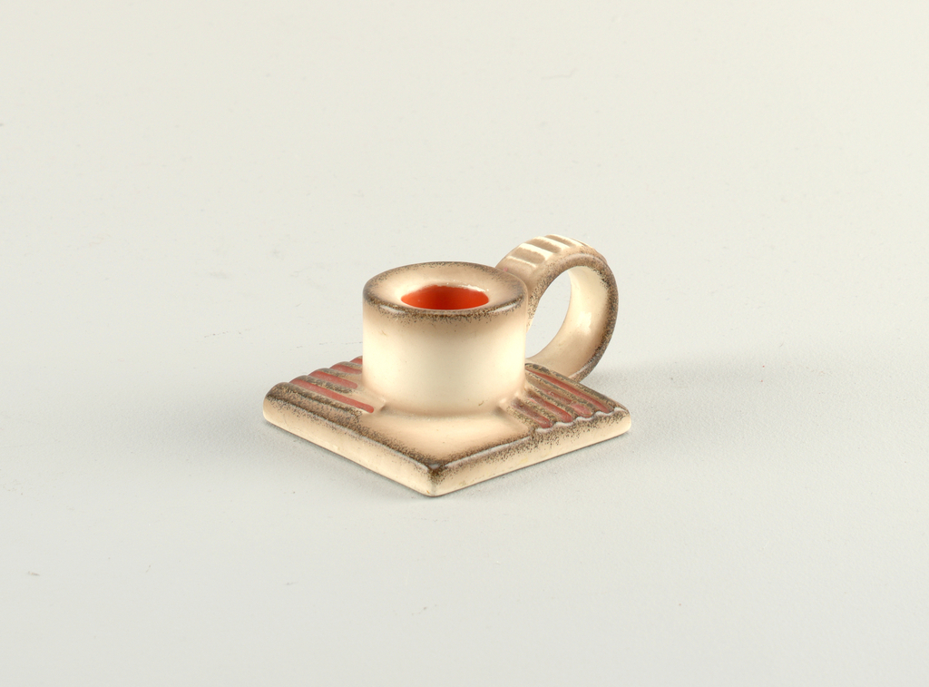 Short candle holder with red glazed interior on ridged square base. Loop handle.