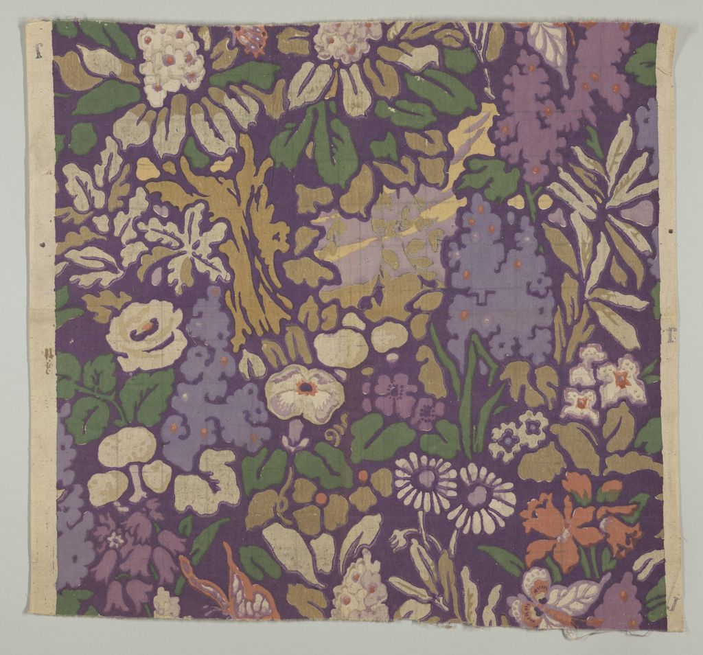 Multicolored block printed fabric with a dark purple ground has a dense allover floral pattern of lavender flowers, white daisies, salmon-colored daffodils, and tan and green leaves. Pattern repeat is a one-half drop.