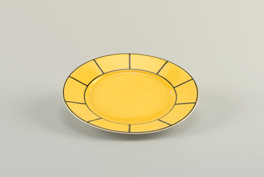 Circular plate with a raised bottom rim.  Also a yellow ground on the top surface with black circular lines from the center and six radiating black lines stretching out to the another black line on the edge.