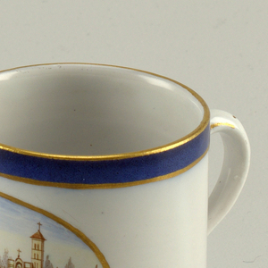 """Short cylindrical cup (a) with loop handle; gray-white ground decorated with underglaze-painted oval medallion showing  view of walled city along riverbank; rim with underglaze blue band between two thin gilt lines; three incised concentric lines around base; handle with gold """"U"""" and dots. Circular saucer (b) with gray-white ground decorated circular central medalion showing view of walled cities on water; rim with underglaze blue band between two thin gilt bands."""
