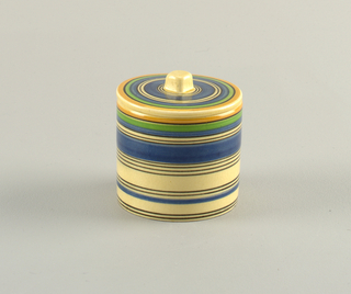 Round cylindrical box with flat lid topped by a square finial.  Cream background with rings of varying width in orange, blue, green, and black.  Matching lid with cream ground and concentric circles in orange, black, green, and blue with a cream finial.