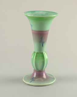 Flaring cup on a spreading base with a large ribbed bead. Green and pink glaze with scattered geometric motif in blue.