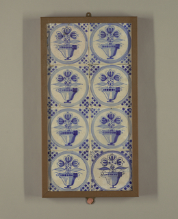 Set of 8 tiles, mounted in rectangular frame, 2 across, 4 down; each painted in underglaze blue on white with 3 tulips in pot in roundel, surrounded by dot and line corner motifs.