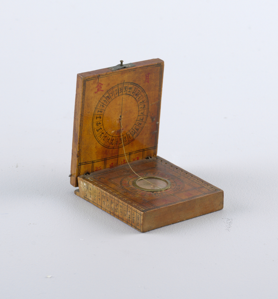 Two rectangular pieces of varnished wood, hinged together with wire, and painted with discs and Chinese numerals in black and red. Compass sunk in glazed center of tower piece. Brass wire stretched between the two pieces serves as sun dial indicator.