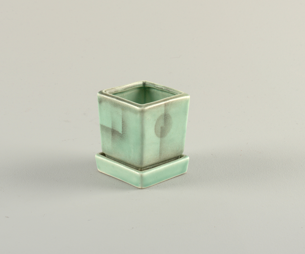 Cubic vessel fitted into a low square tray.  Light green glaze with pale atomized glaze decoration showing abstract designs.
