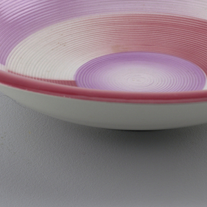 Round plate with a red rim and alternating short, wide stripes of red and purple, with a slightly purple center.