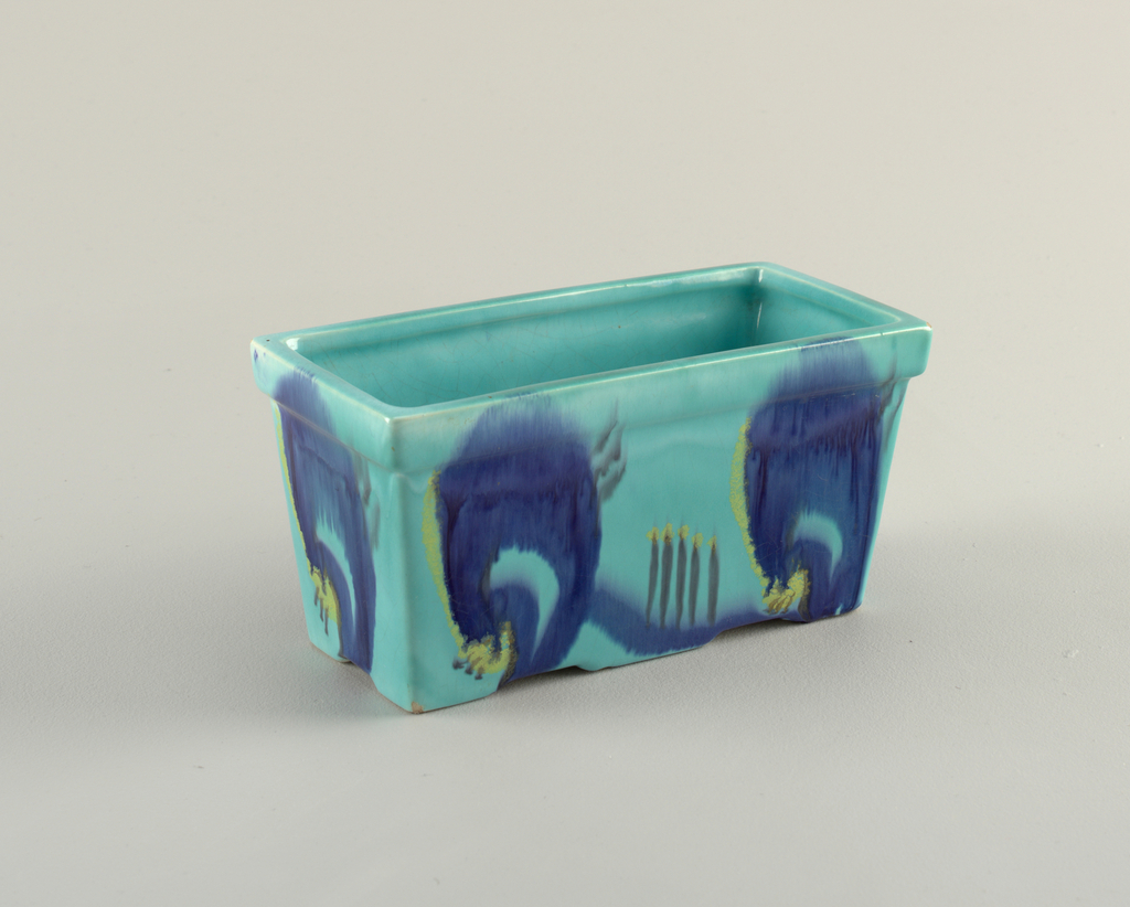 Planter in turquoise decorated with royal blue and yellow floral design.