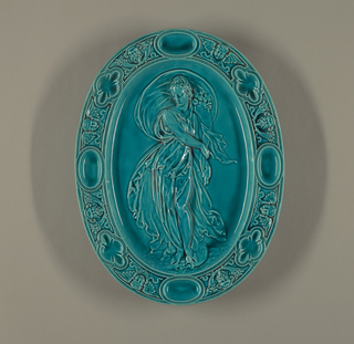 Oval, glazed obverse and reverse, with transparent turquoise lead glaze. Molded with relief border of satyrs' masks, winged putto heads, oval wells and quatrefoil wells, all arranged in repeat sequence within rim of platter. Plain cavetto. Central area molded with large high relief female figure in flowing garments, with foot on water jug.