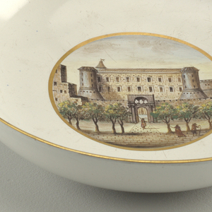 Gold and blue rimmed bowl; at center, a view of a white brick palazzo, flanked by two towers, facing a garden with figures.