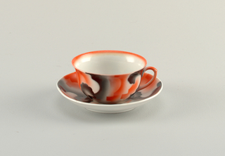 Round cup and saucer with atomized red and black glaze in amorphous design on a white ground. Undecorated inside cup and bottom of saucer.