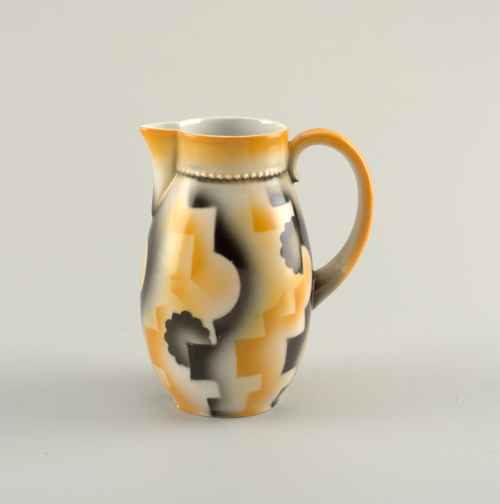 Bulbous cylindrical pitcher with a circular, vertical flat band at top joined to body by a line of molded beading with a triangular spout at mouth sitting across from a C-shaped handle.  Cream ground with orange painting on the top band, spout, and handle. Surface airbrushed pattern of lines, circles, and shapes in orange and black.