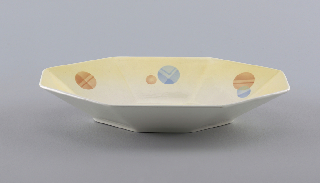 Octagonal concave dish, primarily rectangular in form.  Cream exterior with yellow interior edge that fades gradually to a cream center.  Six side panels patterned alternately with one or two circles of orange and blue decorated with abstract lines.