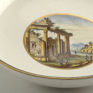 Gold and blue rimmed bowl; at center, a landscape with figures among overgrown ruins.