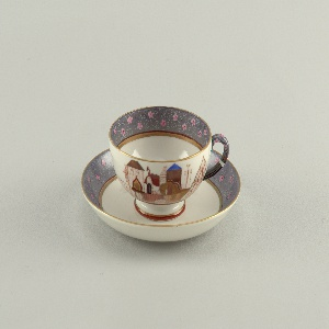 Cup rounded, tapering at base to raised foot; loop handle; painted with band of architectural motifs consisting of houses, churches, etc. Saucer round, with slightly raised rim; painted with a border of pink flower blossoms against a spiral-patterned background.
