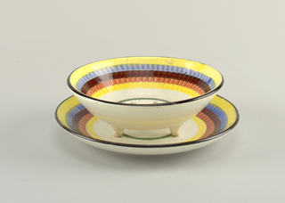 Circular bowl standing on three conical feet with thirteen holes in the bottom .  Edge painted black and then descending concentric circles to the center of: yellow, blue, brown, rose, yellow, white, green, and a round white center.  Bowl matches circular dish on a raised bottom rim.  Dish has a black edge and then interior concentric circles of: yellow, blue, brown, rose, yellow, white, green, and finally a round white center.