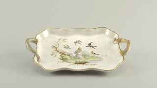 Shaped oblong dish with scrolled handles at either end. Center decorated in pale colors with a group of birds centered on an owl, in front of a stream. Edge and handles gilded.