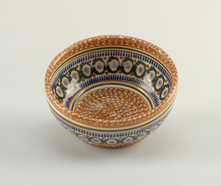 Round bowl with mottled orange ground with patterned band of circles and stripes in blue and green.