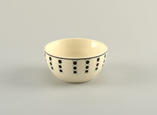 Round bowl with side sides. White ground decorated with large black and small teal dots. Black line at rim.