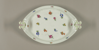 Oval dish with molded scrolling handles and decorated with scattered flowers.