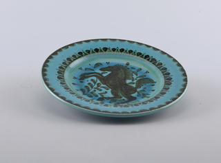 Round plate with painted black horse and foliage in the cavetto. Blue glaze ground.