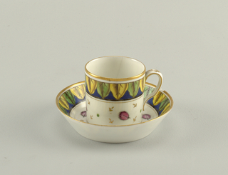 Cylindrical cup with slightly scrolled handle. Saucer flat, with flaring edge. Decorated in gold and thick overglaze enamel. Band of half leaves about edge of cup and saucer.