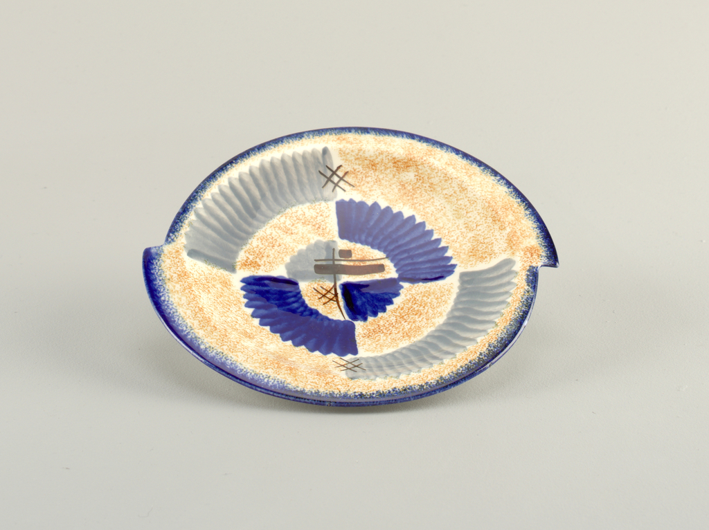Asymmetrical plate appearing as if two semi-circles were joined together about one inch off sides, with raised bottom rim and flat top edge.  White background speckled with orange.  Edge lined in deep blue.  Abstract pattern consists of modulated patches of blue and gray.  Four areas of brown crossed straight lines.  Centered opposite quarter circles, one of blue and one of gray.