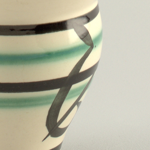 Tall vase with wide center; flared open mouth. Decorated with black rim, black horizontal lines, green lines and leaf motif in black on light pink ground.