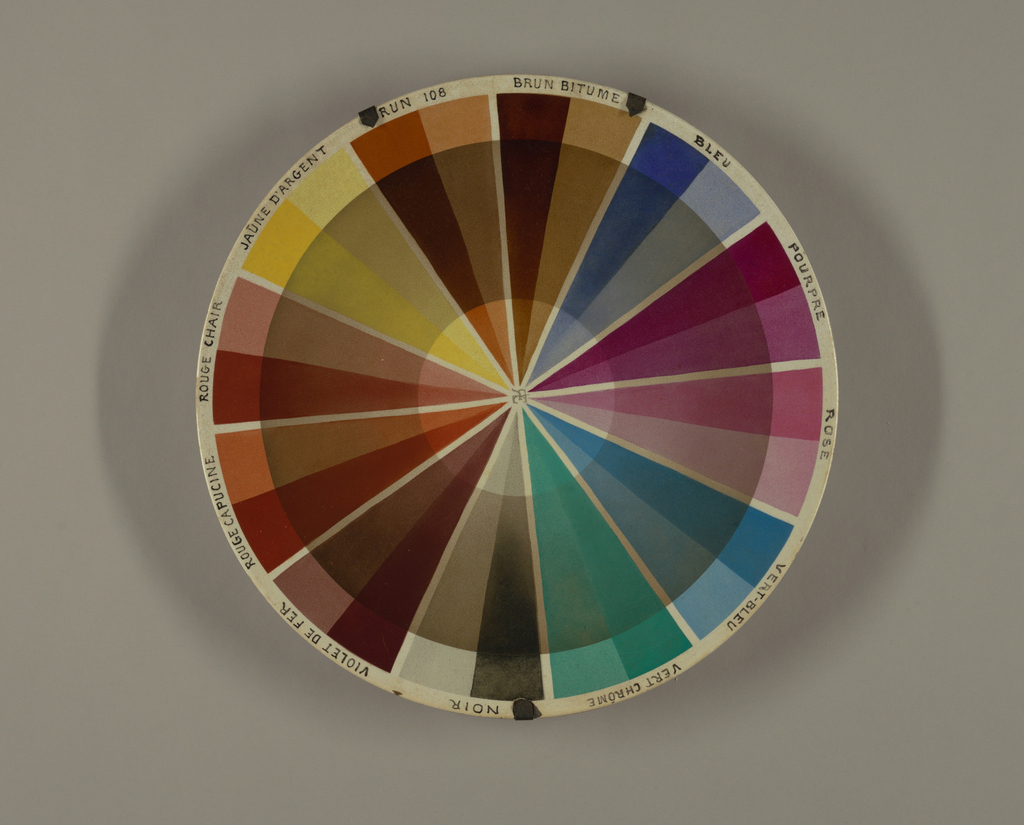 """Circular, slightly concave plate with 12 pie-wedge sections of various colors in light and dark hues; names of colors in French around rim, above each wedge (starting at top going clockwise):  """"ROSE, VERT-BLEU, VERT CHRÓME, NOIR, VIOLET DE FER, ROUGE CAPUCINE, ROUGE CHAIR, JAUNE D'ARGENT, BRUN 108, BRUN BITUME, BLEU, POURPRE""""; wide circular band of tan glaze overlaps wedges, creating sections of tinted colors; in center of plate, overlapping initials """"R[backwards]EC"""" in tan glaze.  Plate mounted in hanger of three metal straps and wire."""