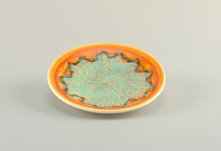 Round plate with flat orange rim. At center, green glaze with orange details.